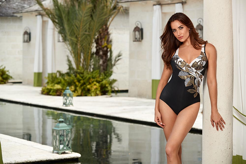 a7bfb3955 MIRACLESUIT S surplice maillot in black is accented with beautifully  engineered florals and shimmering metallics.